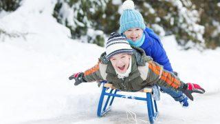 Two little boys sledding on snow.
